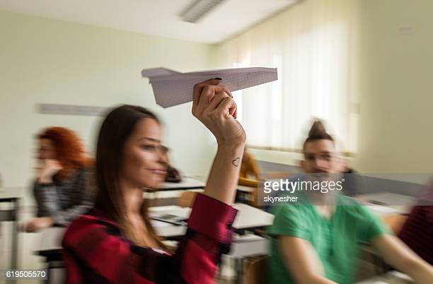 Student in blurred motion throwing paper airplane in the classroom.
