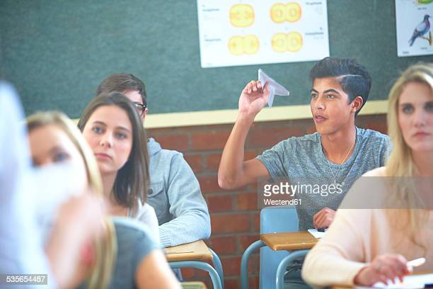 Student in classroom throwing paper plane