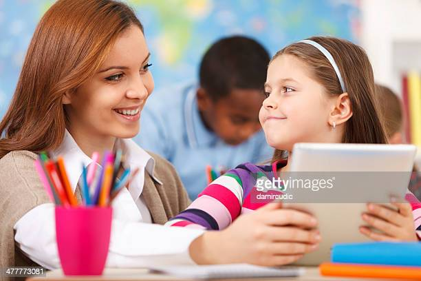 Student In Classroom Using Digital Tablet With Teacher