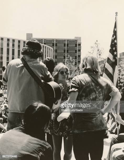 Student in hippie attire holding a guitar prepares to play for a large group with American flag visible during an anti Vietnam War student sitin...