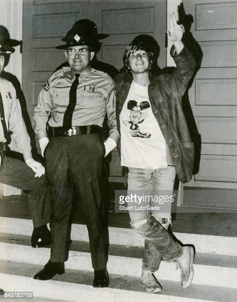 Student in hippie attire including a tshirt with a caricature of politician Spiro Agnew portraying Agnew as the character Mickey Mouse posing with...