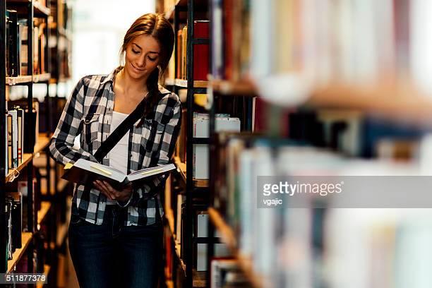 Estudante na biblioteca e olhando o livro corredor
