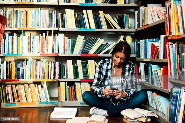 Studentin in der Bibliothek hören Musik