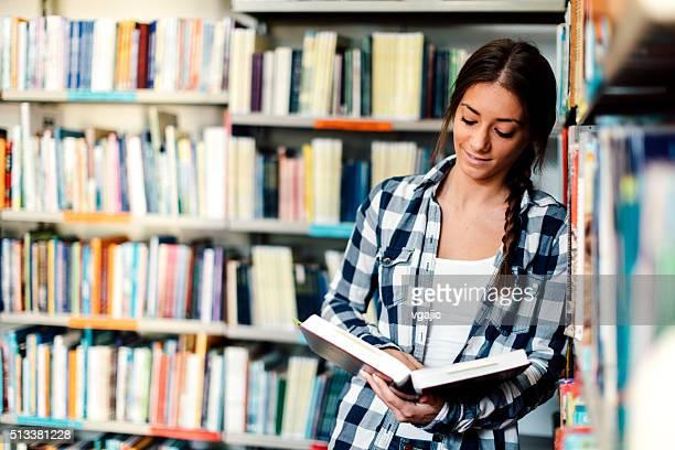 Aluno a ler um livro na biblioteca.