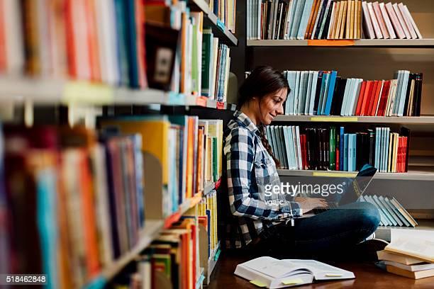 Estudante na biblioteca usando computador portátil.