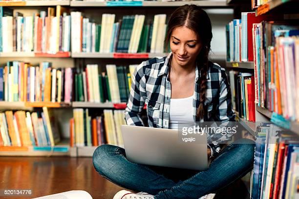 Estudante na biblioteca com computador portátil