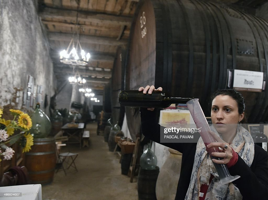 A student in wine tastes a blend of grapes from the ' Domus-Maximus' Chateau Massamier La Mignarde wineyard in the cellar of the domain in Pepieux southwestern France, on May 21, 2014 . AFP PHOTO / PASCAL PAVANI
