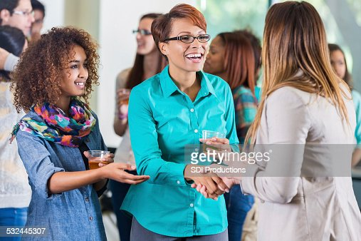 Student introducing parent to teacher during meet and greet party
