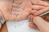 Student is cheating during exam with cheat sheet with formula written on his hand.
