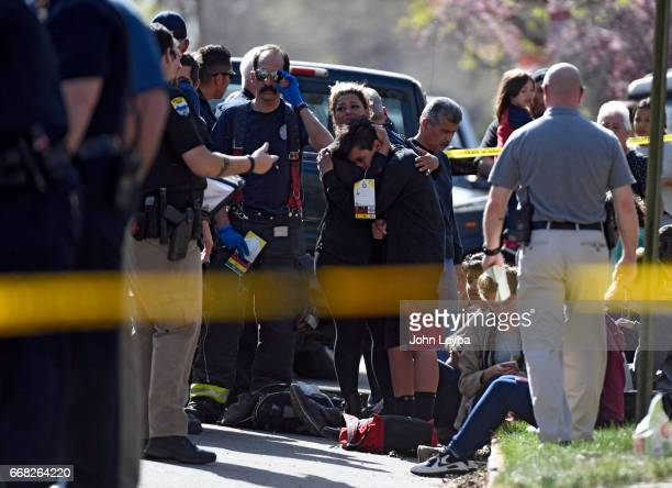 A student is consoled as paramedics work on kids at 39th Tejon after their bus they were in was hit by a Grand Cherokee on April 13 2017 at The...