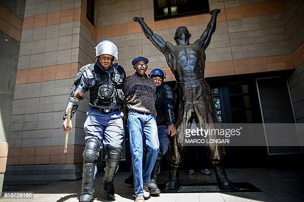 TOPSHOT A student is detained by a South African ant riot policeman after he entered a building of the Witwatersrand University in Johannesburg on...