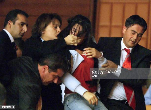A student is escorted out by security members on November 13 2009 following a protest in Ankara Turkish parliament is set to discuss details of a...