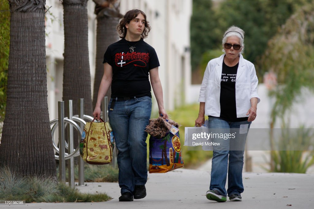 A student (L) is escorted through Santa Monica College, which remains closed for a second day as investigators gather evidence from crime scenes, to pick up personal belongings that were abandoned when a gunman on a mass shooting spree entered the campus, on June 8, 2013 in Santa Monica, California. The shootings occurred in various locations about three miles south of a political fundraiser attended by President Barack Obama but Secret Service officials said the two events were not related and that the president was never in any danger. Four people besides the gunman have died from their wounds and five others wounded, including a woman who is close to death.