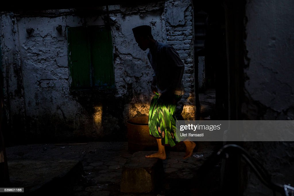 A student is silhouetted as he walks at the islamic boarding school Lirboyo during the holy month of Ramadan on June 11, 2016 in Kediri, East Java, Indonesia. The Islamic boarding school, Lirboyo, was founded by KH Abdul Karim in 1910, and known to be one of the largest traditional 'Pesantren' in Indonesia, with around 17,000 students in Kediri, East Java. Students at the Pesantren, also known as 'Santri', are separated from their families and spend their days studying Islamic scriptures, reading the Quran and learning Arabic in addition to other activities which begins with the morning prayer at 4am till midnight.