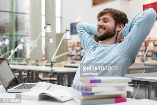 Student leaning back in a university library
