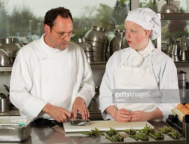 Schüler lernen Sie kochen von einem erfahrenen Trainer.