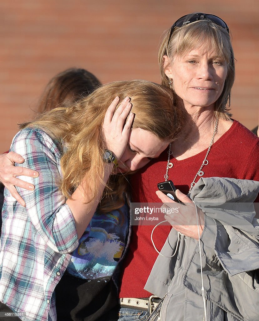 CENTENNIAL, CO - A student leaves Euclid Middle School with her parents after getting bused their from Arapahoe High School December 13, 2013. A gunman at the school was targeting a teacher at the school. The gunman shot two students in the process and then turned the gun on himself.
