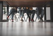 Lower body of young people sitting at the table. They are wearing casual clothes and sport shoes. Low angle. Copy space