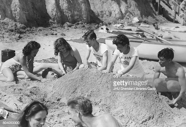 Student Life Beach Party Senior Week Candid shot of students and their girlfriends burying a student in the sand at Triton beach 1947