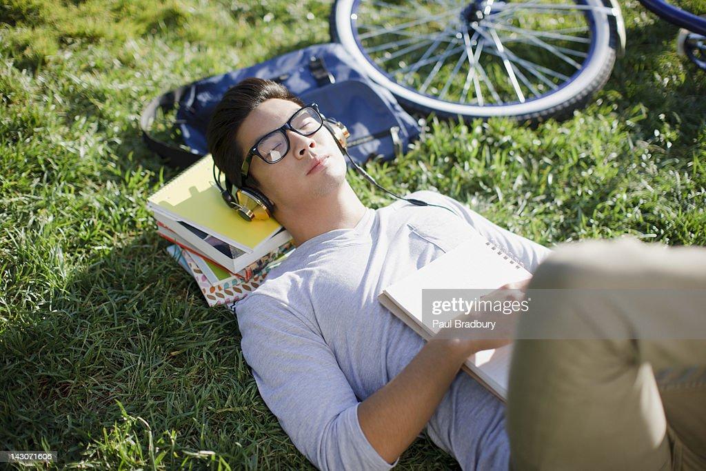Student listening to headphones in grass : Stock Photo