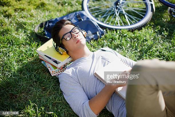 Étudiant à l'écoute au casque audio en herbe