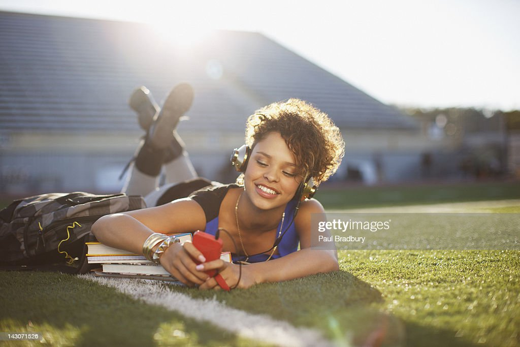 Student listening to mp3 player in grass : Stock Photo