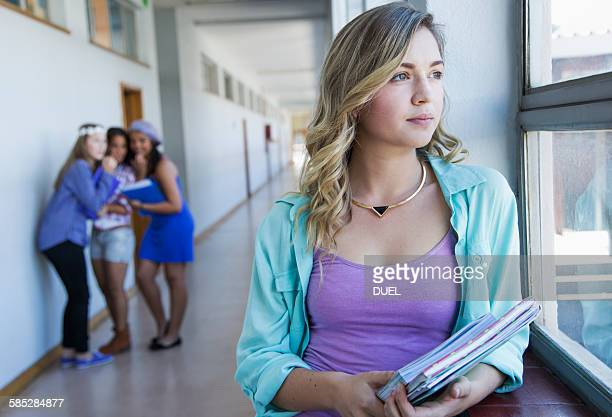 Student looking out window, friends gossiping in background