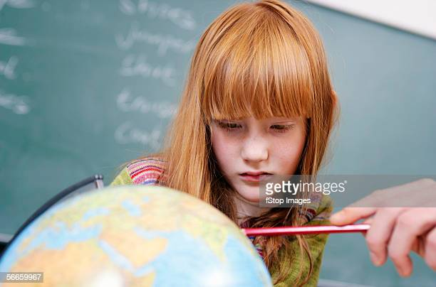 A student looks attentively at a globe with her teacher