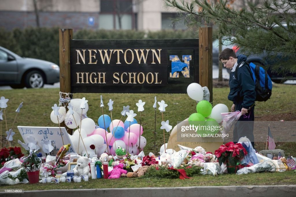 A student looks for a place to leave flowers at a makeshift memorial for the victims of the Sandy Hook Elementary School shooting at the entrance of Newtown High School December 18, 2012 in Newtown, Connecticut. Students in Newtown, excluding Sandy Hook Elementary School, return to school for the first time since last Friday's shooting at Sandy Hook which took the live of 20 students and 6 adults. AFP PHOTO/Brendan SMIALOWSKI