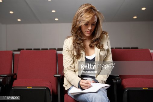 Student making notes in lecture theater