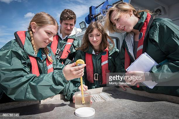 Student marine biologists test sea water sample on research ship