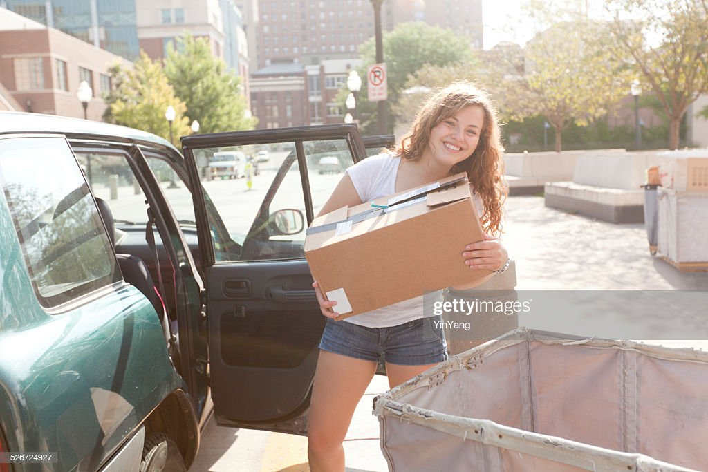 Student Moving Box from Car to Dormitory on College Campus