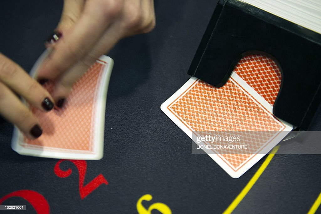 A student of the Cerus Casino Academy, a school for croupiers, deals out cards on a black jack table in Paris, on February 27, 2013. AFP PHOTO / LIONEL BONAVENTURE