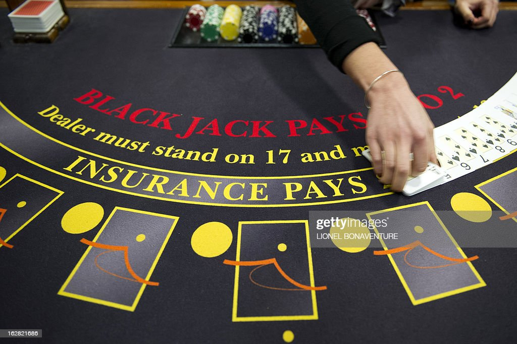 A student of the Cerus Casino Academy, a school for croupiers, deals out cards on a black jack table in Paris, on February 27, 2013.