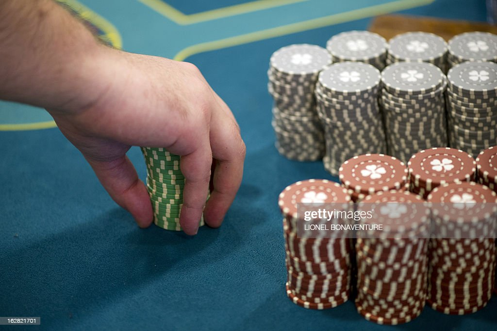 A student of the Cerus Casino Academy, a school for croupiers, deals out tokens on a black jack table in Paris, on February 27, 2013.