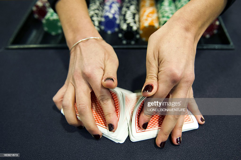 A student of the Cerus Casino Academy, a school for croupiers, shuffles cards on a black jack table in Paris, on February 27, 2013.