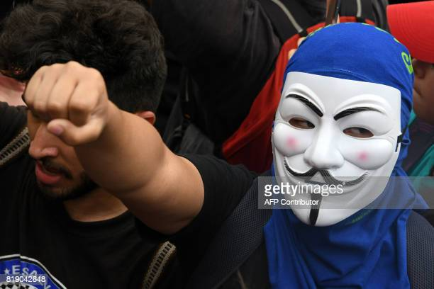 A student of the National Autonomous University of Honduras wears a Guy Fawkes mask during a march to demand among other things the resignation of...