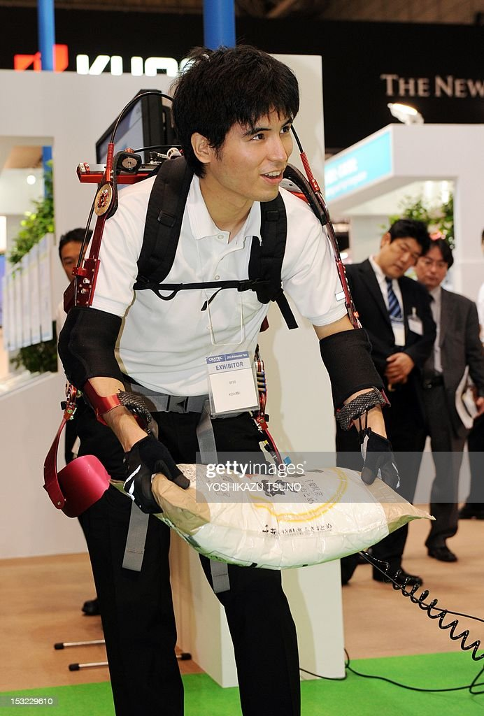 A student of the Science University of Tokyo demonstrates a robotic 'Muscle Suit', developed by professor Hiroshi Kobayashi and powered by compressed air to assist the muscular ability of nursing carers and manual workers, at Asia's largest electronics trade show CEATEC (Cutting-Edge IT & Electronics Comprehensive Exhibition) in Chiba, suburban Tokyo on October 2, 2012. Some 600 Japanese and foreign companies exhibited their latest technology and products. AFP PHOTO / Yoshikazu TSUNO