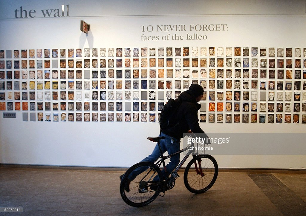 A student on a bicycle passes portraits of US soldiers killed in Iraq on the first day of the exhibition 'To Never Forget The Faces of the Fallen' in...