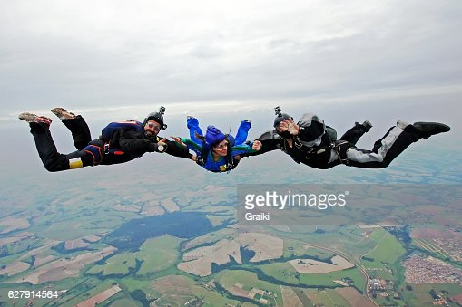 A student on her first jump with two instructors.