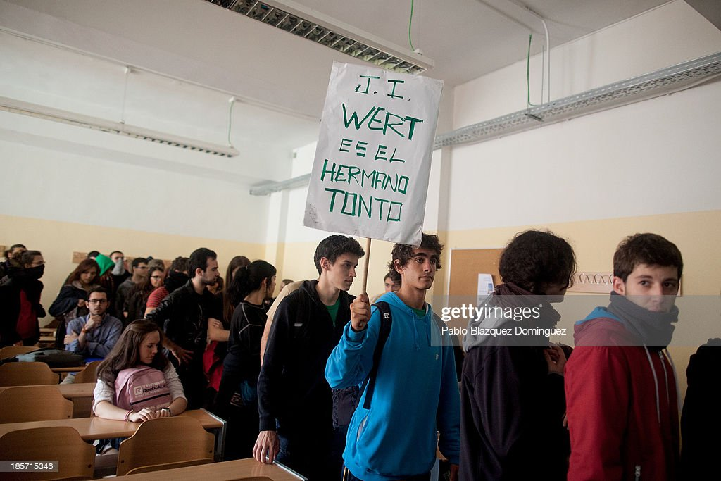 A student on strike holds a placard reading 'Jose Ignacio wert is the silly brother' in a classroom while other students sit at their desk in the School of Aeronautic Engineers in Ciudad Universitaria on October 24, 2013 in Madrid, Spain. The Spanish Parliament recently approved a controversial reform of the educational system, which passed by the ruling right wing People's Party (PP) using their absolute majority and not backed by any other political party. The students are on a three day strike to protest against the new law, which will need to be approved by the senate next month and are calling for the resignation of Education Minister, Jose Ignacio Wert.