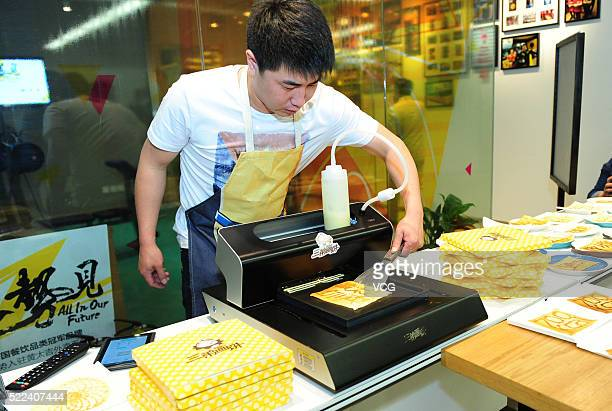A student operates a 3D printer to print various types of pancakes on April 19 2016 in Beijing China The 3D printer was developed by students from...