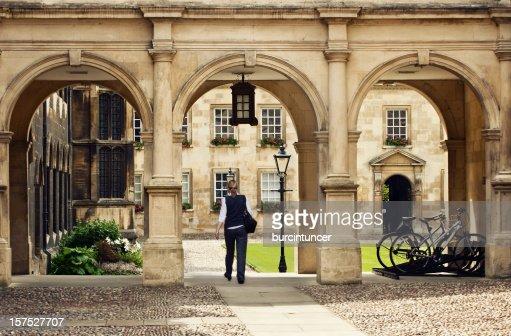 Student passing through a college campus in Cambridge Universitiy, UK