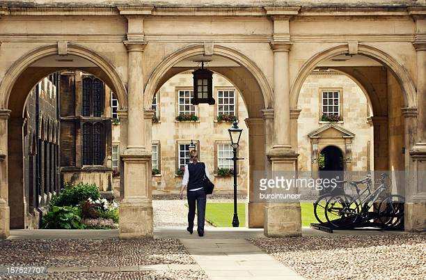Student passing through a college campus in Cambridge Universitiy, UK