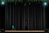 Student peering from behind curtain on stage