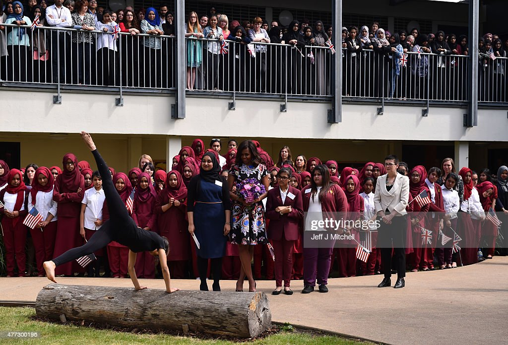 A student performs a gymnastic routine as young women hold the American flag as they greet US First Lady Michelle Obama in the courtyard before an event as part of the 'Let Girls Learn Initiative' at the Mulberry School for Girls on June 16, 2015 in London, England. The US First Lady is travelling with her daughters, Malia and Sasha and her mother, Mrs. Marian Robinson, to continue a global tour promoting her 'Let Girls Learn Initiative'. The event at the school was to discuss how the UK and USA are working together to expand girl's education around the world.
