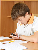 Boy sending text messages friends on his cellphone, because he don't want to learn
