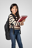 Young asian girl standing and holding books, Isolated on grey background