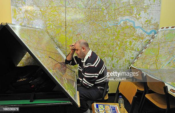 A student ponders while drawing routes on a map of London in a test centre in north London on February 28 2013 All London Black Cab drivers are...