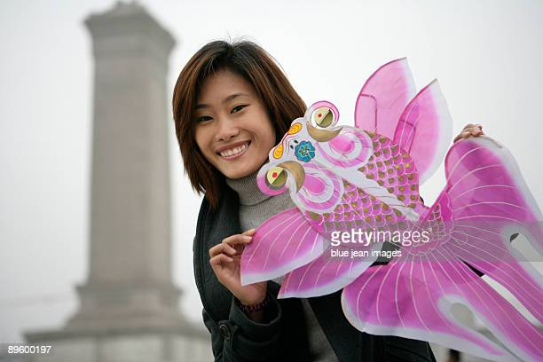 Student posing with kite in Tiananmen Square, Beijing, China